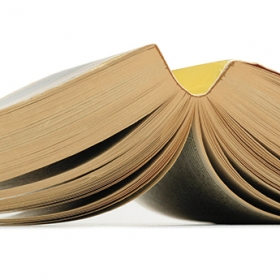 A photo shows an open paperback book, splayed face down.