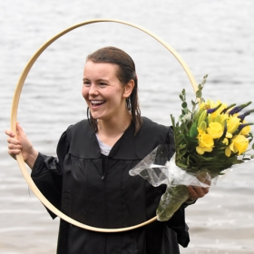 Paige Hauke '19, the hooprolling race winner, holds her hoop and a bouquet of yellow flowers in Lake Waban.