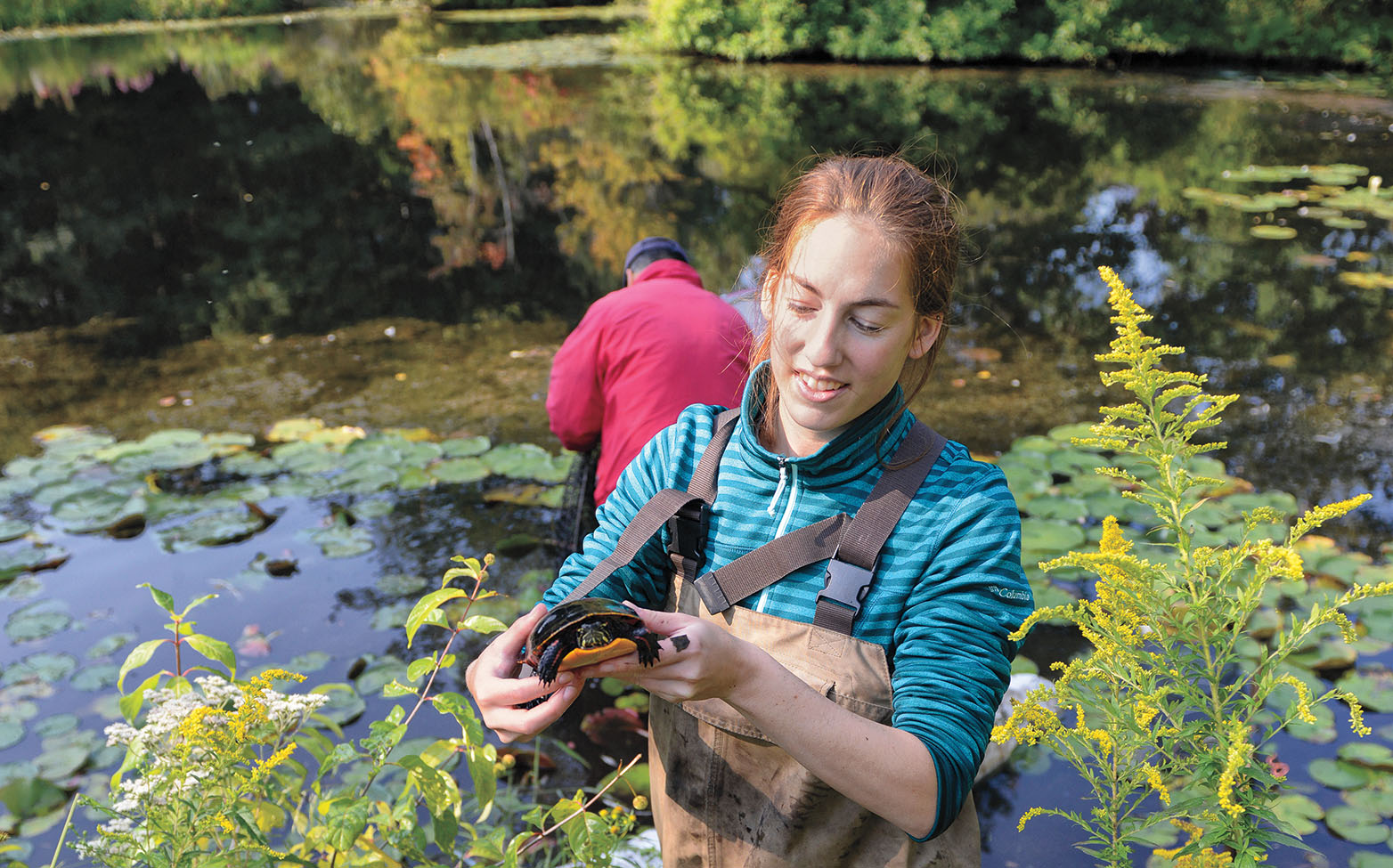 A photo of a student holding a turtle beside Paramecium Pond.