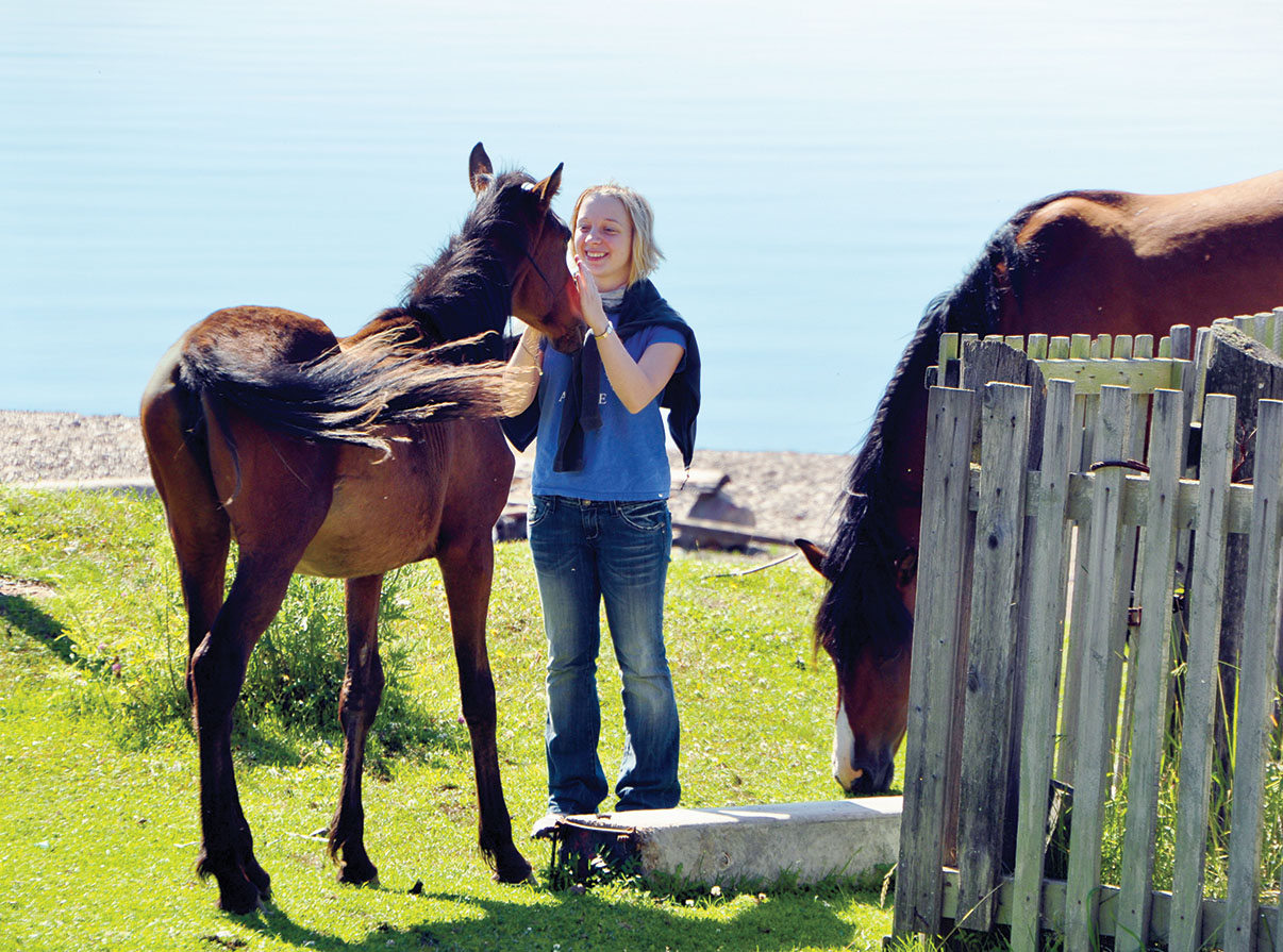Elena Mironciuc '13 makes friends with horses on the beach at Bol'shie Koty in 2011.