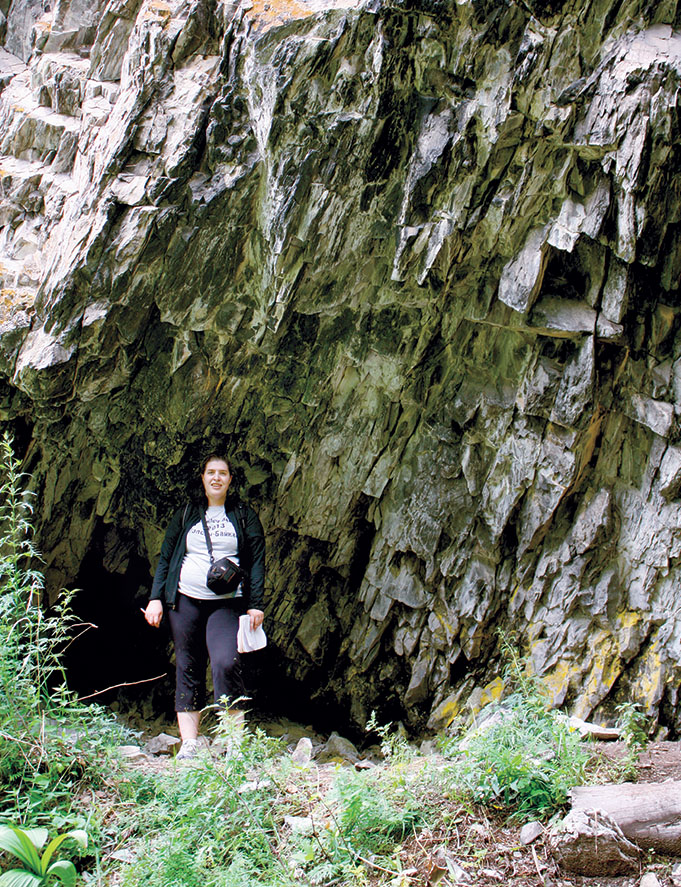 A student poses at the entrance to a mountain cave above the Bol'shaia Kadilnaia Valley in 2009.