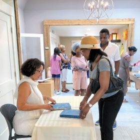 A photo shows Cheryl Finley '86 signing books at the Featherstone Center for the Arts in Oak Bluffs, Mass.