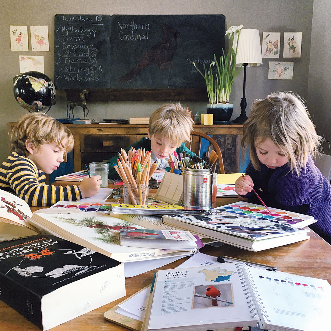 A photo of the author's three children painting with watercolors