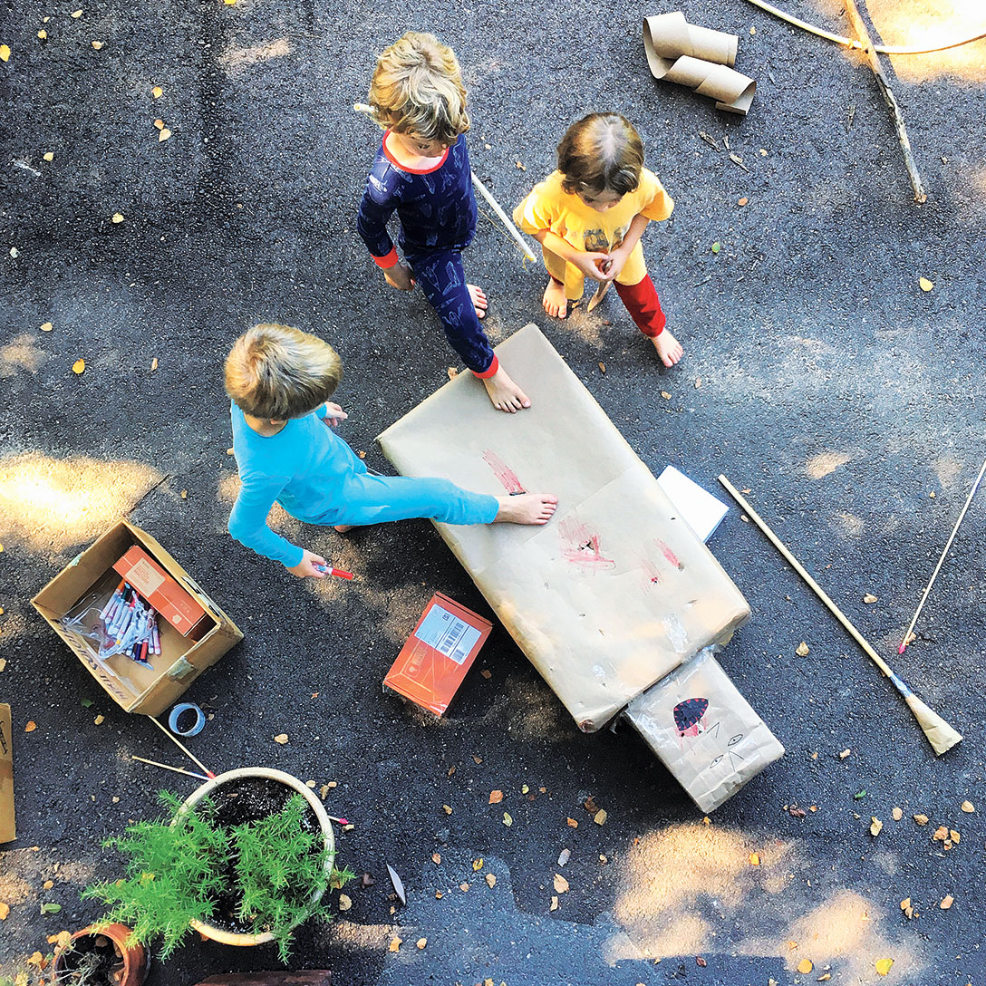 The authors' children working out-of-doors, building a structure with boxes