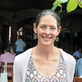 A photo portrait of Alissa Carlat Ruxin '97shows her standing in front of her restaurant, Heaven.