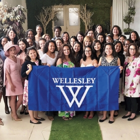 A photo shows members of WAAD and WLAN dressed up and gathered for their annual tea in L.A.