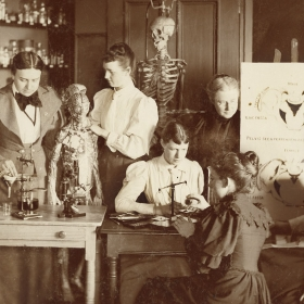 A photo from the early days of Wellesley of students studying scientific models in College Hall.