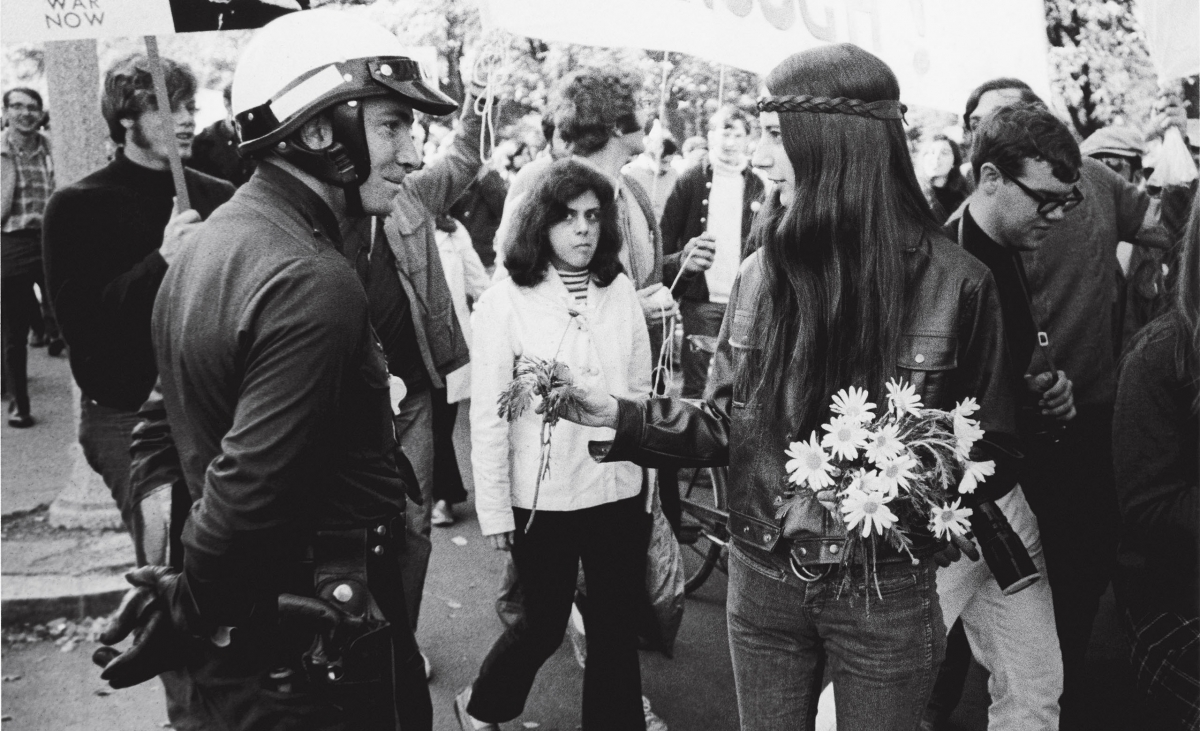 A photo taken at a demonstration in 1970 shows a  a Wellesley student handing a daisy to a police officer.