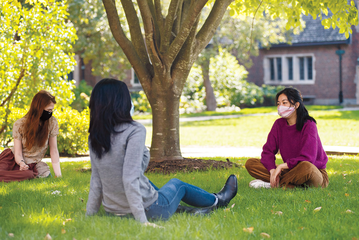 Masked students sit outside on a lawn