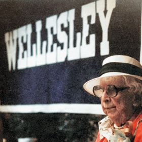 Marjorie Stoneman Douglas 2012, wearing her signature white hat, stands in front of a Wellesley banner.