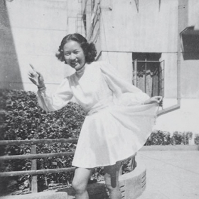 A young woman poses for the camera pointing with one hand while holding up a corner of her skirt in a kind of curtsy with the other