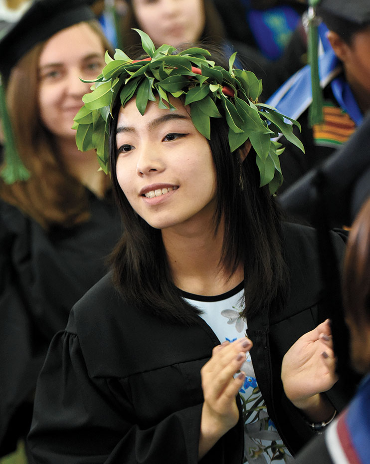 A student wears a crown of elaves