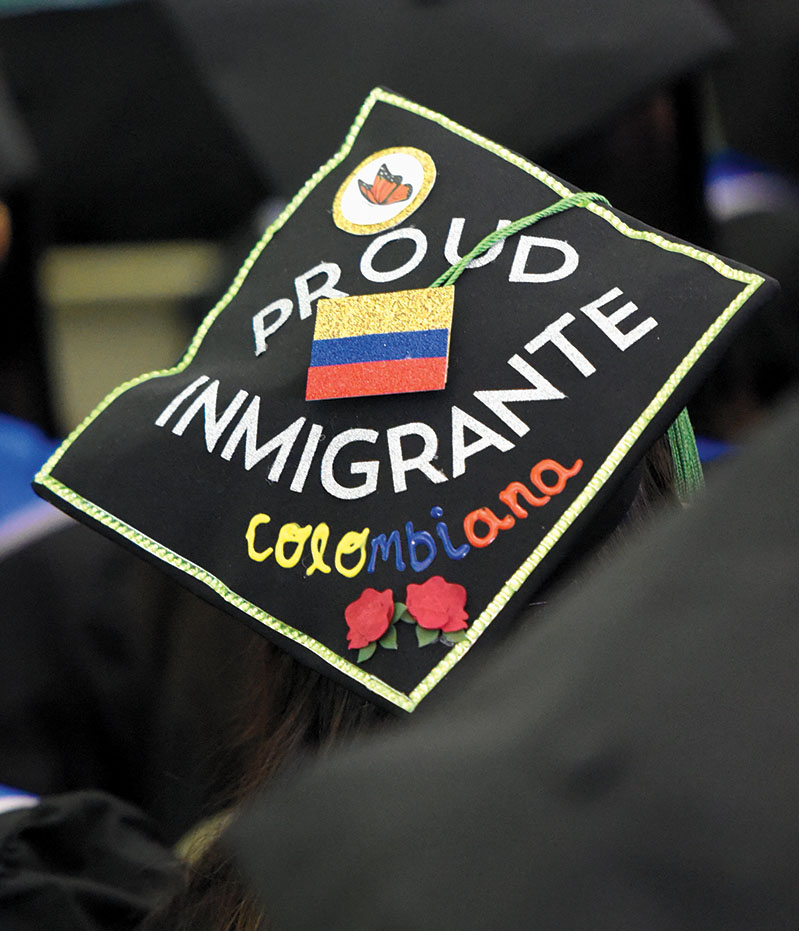 "A student wears a hat that says ""Proud Immigrante"""
