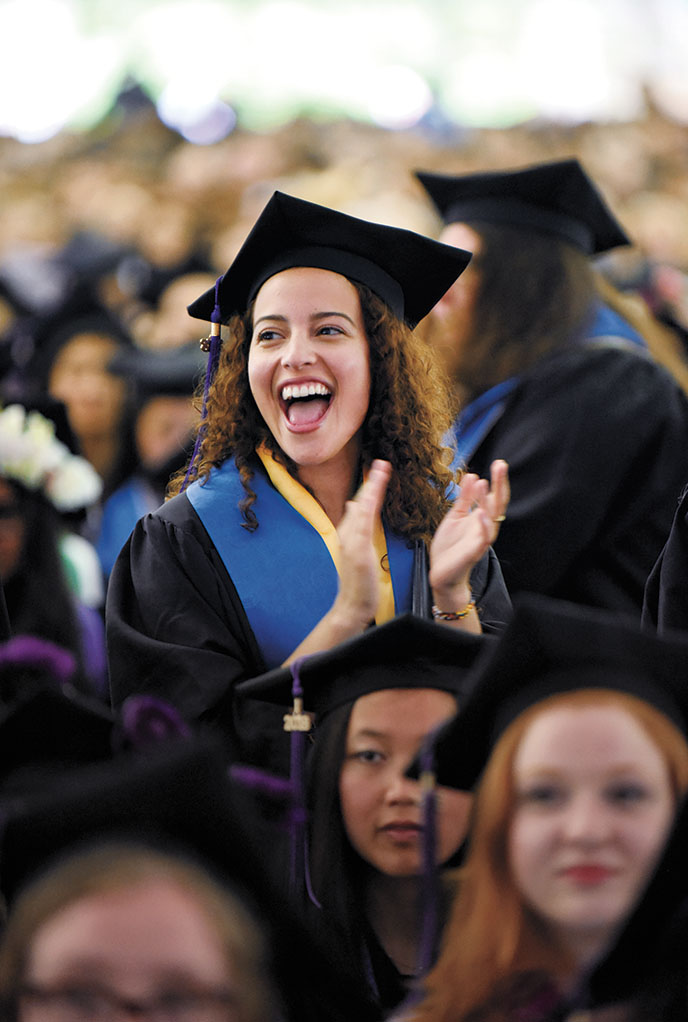 A photo of a graduate standing and cheering during the ceremony.