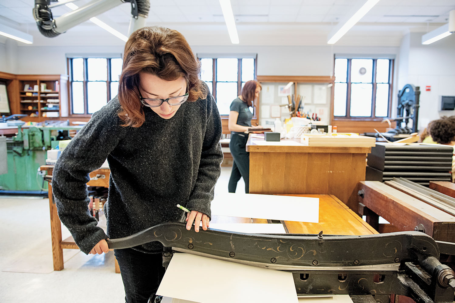 A student cuts paper in the Book Arts Lab