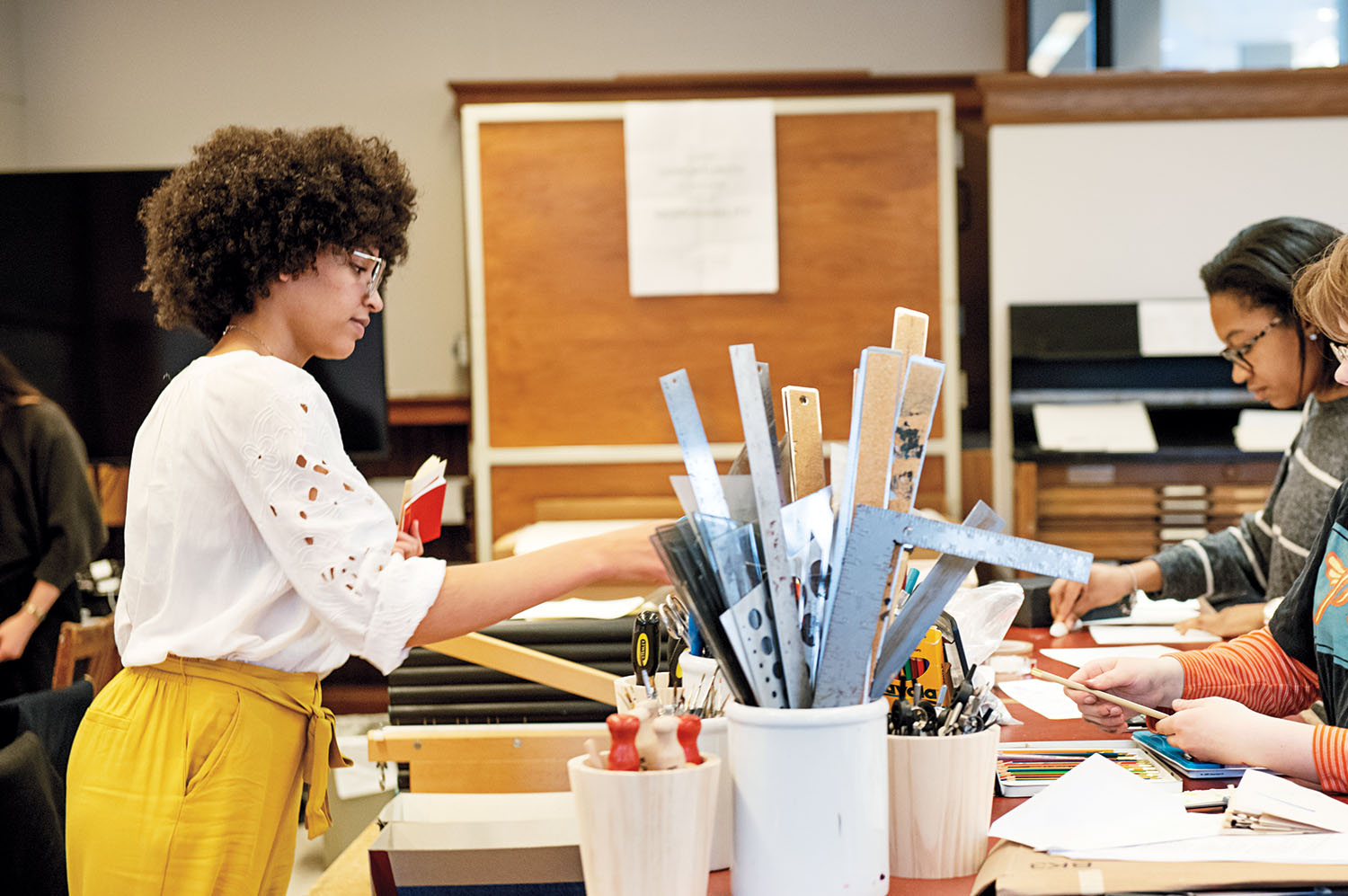 Students work on print projects in the book arts lab
