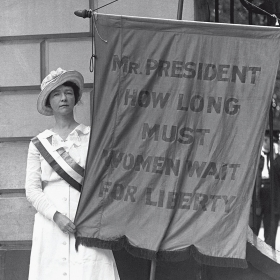 """A suffragist holds a banner reading """"Mr. PRESIDENT HOW LONG MUST WOMEN WAIT FOR LIBERTY"""""""