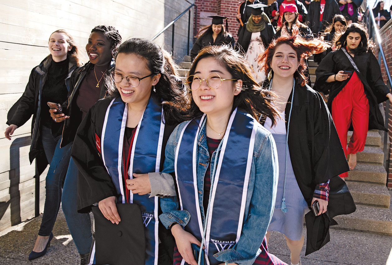 Students march on campus to their informal graduation ceremony