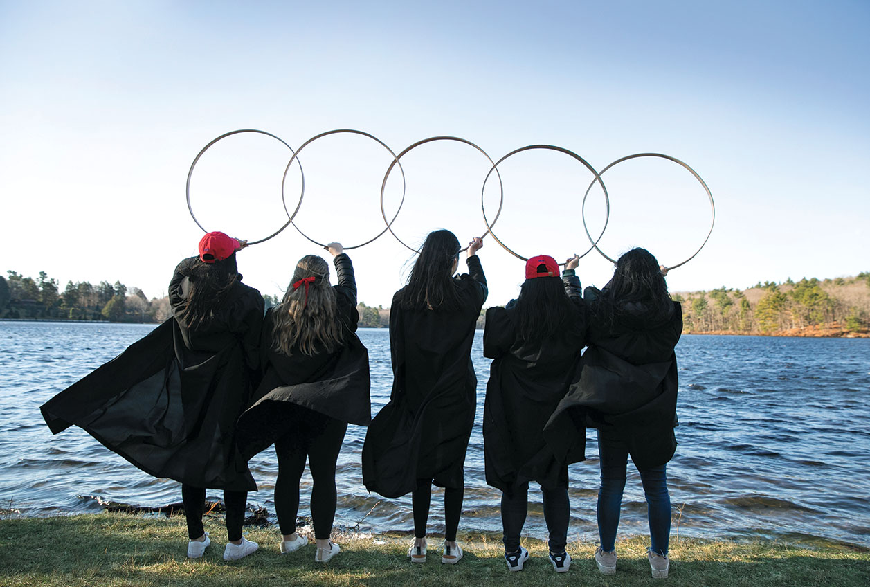 Five friends in graduation robes, their backs to the camera, hold their hoops aloft in front of Lake Waban