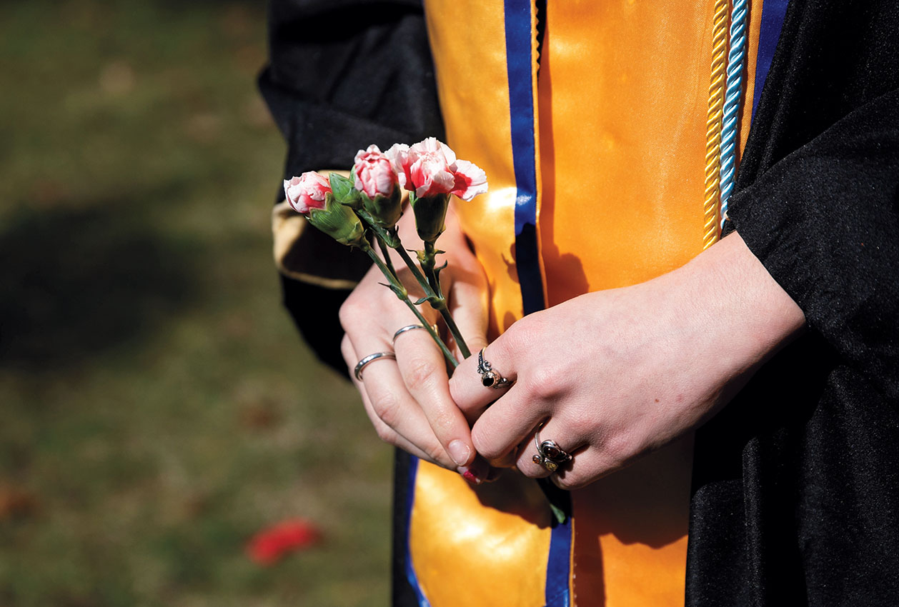 Close up of a student's hands holding a flower