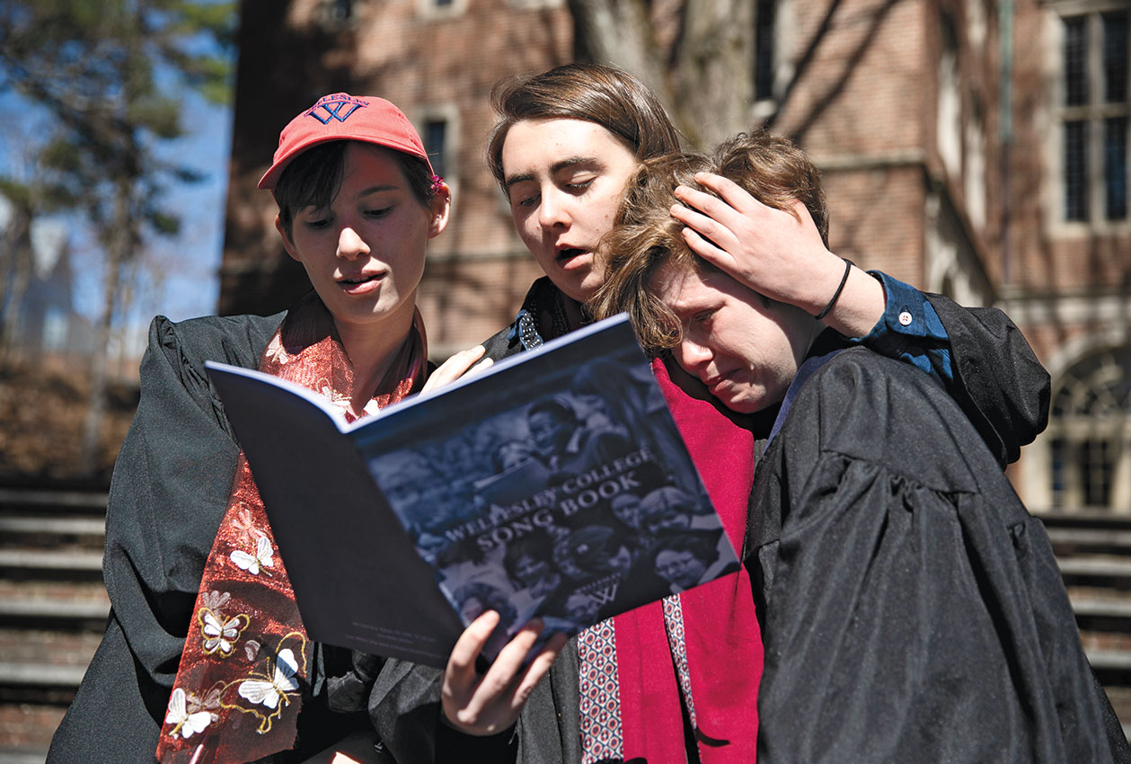 Students sing College songs and hug each other