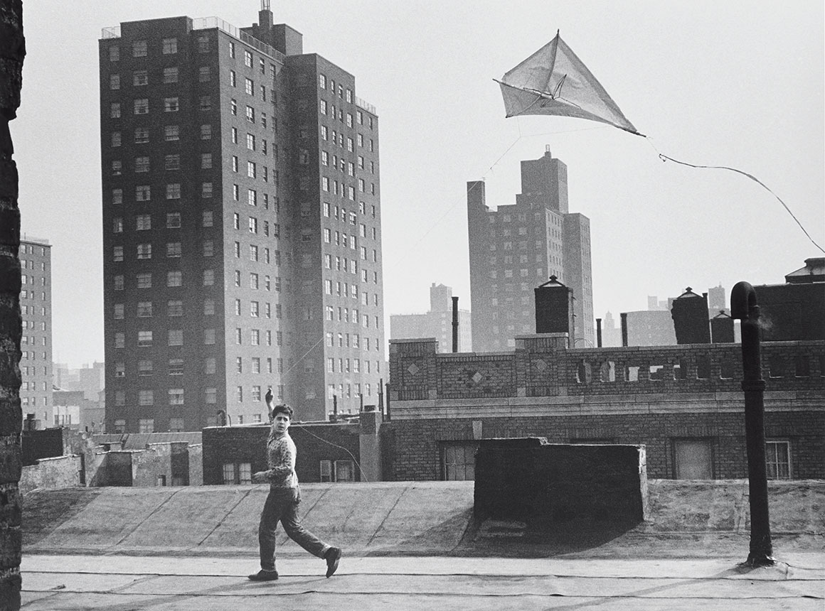 A black-and-white photo of a boy flying a kite on the rooftop in a cityscape