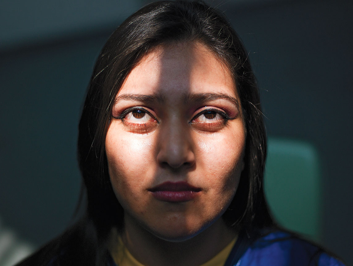 A color portrait of a young woman, a shadow down the middle of her face.