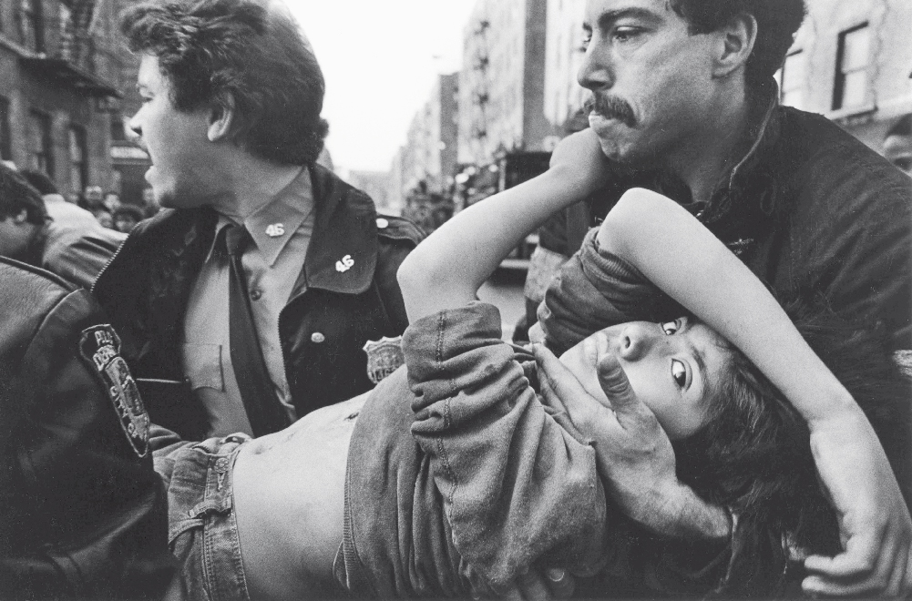 A black-and-white photo of a boy being carried, his arms askew and looking directly at the camera, by two men who appear to be rushing