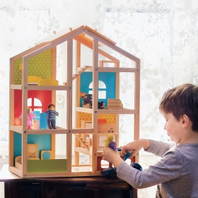 Photo of preschool-aged boy playing with dollhouse