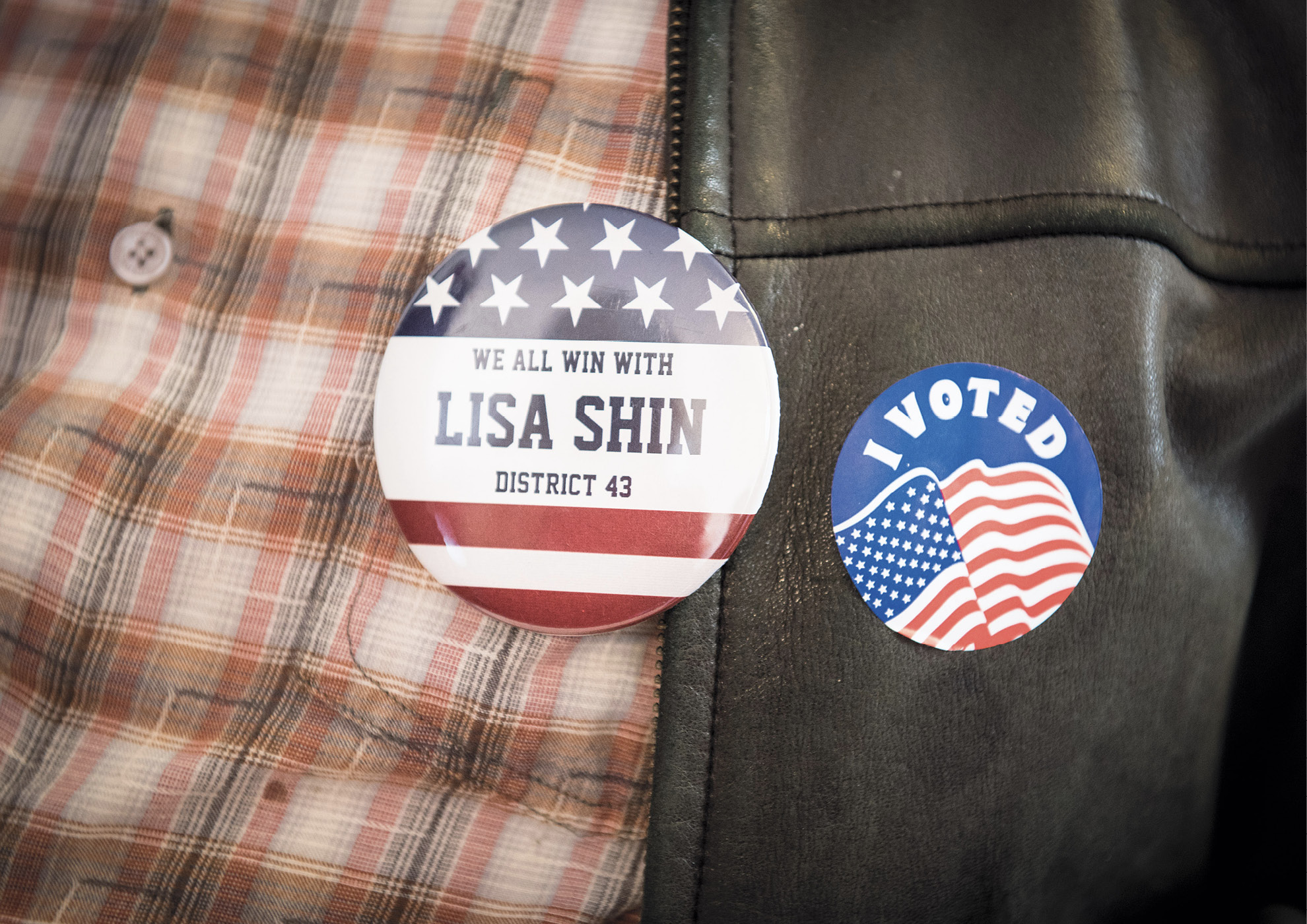 """Close up of pins reading """"We All Win with Lisa Shin District 43"""" and """"I Voted"""""""