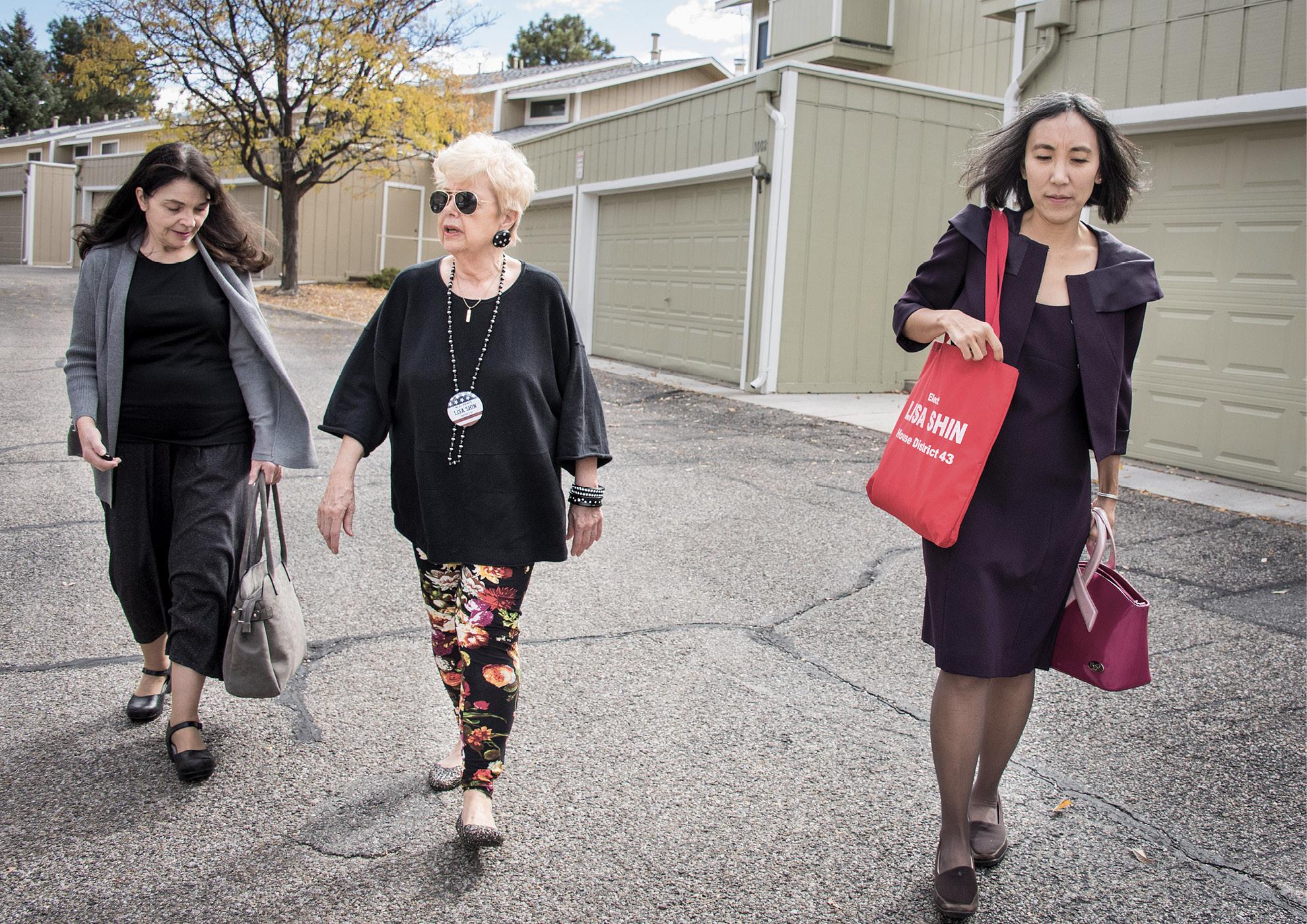 Shin walks with two women across a parking lot between meetings