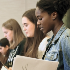 A photo shows five student actors reading student playwrights' work.