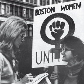 """Lynn Sherr interviewing a participant holding a sign reading """"UNITE"""" with a female symbol and a fist during a women's rights march in 1970"""