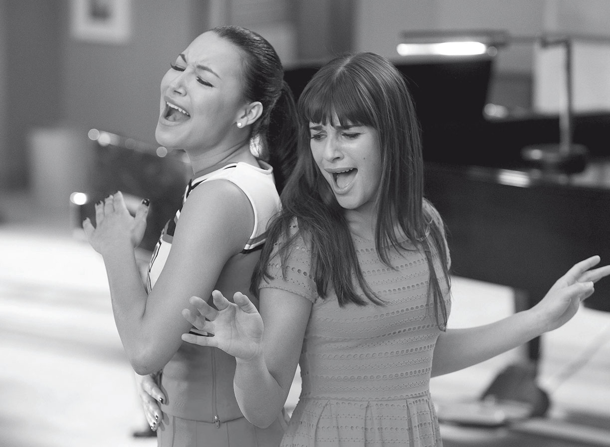 High schoolers Santana and Rachel perform in the musical comedy Glee.