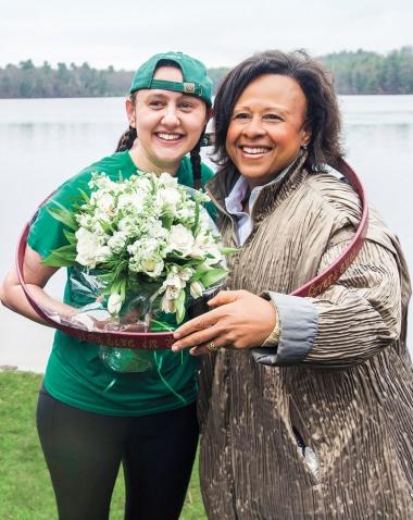 Laurel Wills '17 and President Paula Johnson pose inside Laurel's hooprolling hoop as Laurel holds a bouquet of flowers.