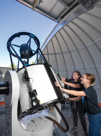 Students adjust the position of the new telescope