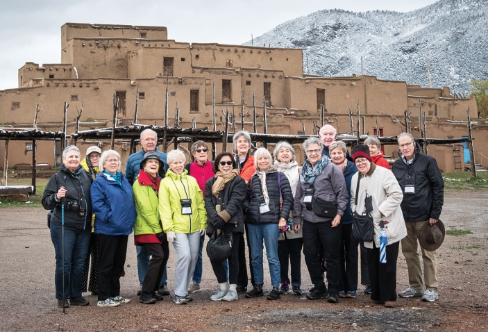 A photo depicts members of the class of '67 in fromt of a pueblo in Taos, New Mexico.