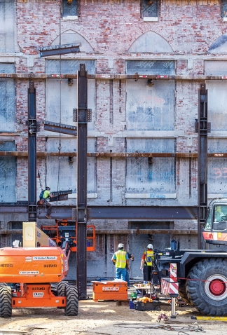 The wall of Sage Hall that forms the Focus is supported by steel beams during the construction of the Science Center
