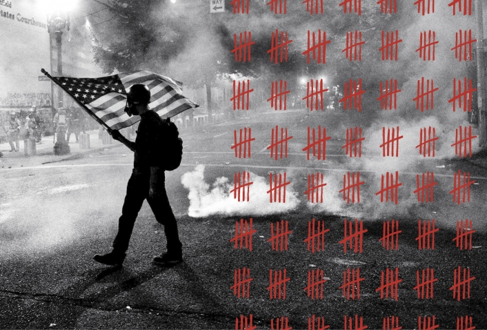 A black-and-white photos depicts a Black Lives Matter protester carrying an American flag as tear gas fills the air outside the Mark O. Hatfield United States Courthouse in Portland, Ore., on July 21.