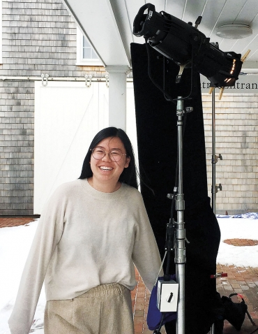 Cathy Ye '19 stands next to professional lighting equipment.