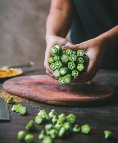 Hands hold a bunch of fresh okra