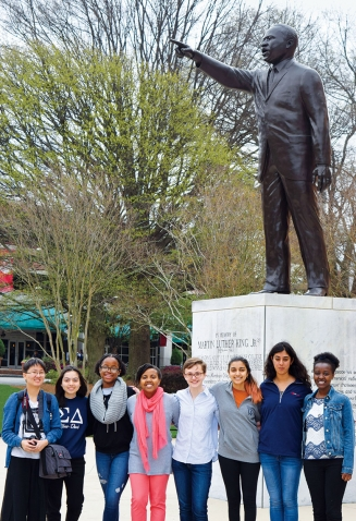 Wellesley students pose in front of a statue of Martine Luther King, Jr.