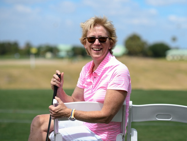 A photo of Leslie Andrews '82,golf club in hand, on the course at Nehoiden.