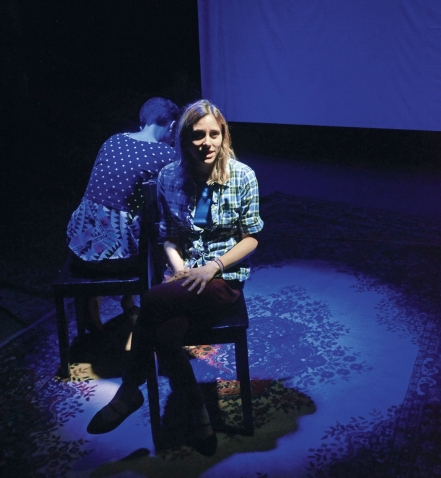 "A photo taken during the production of ""Decisions"" shows two student actresses sitting back-to-back on a dimly lit stage."
