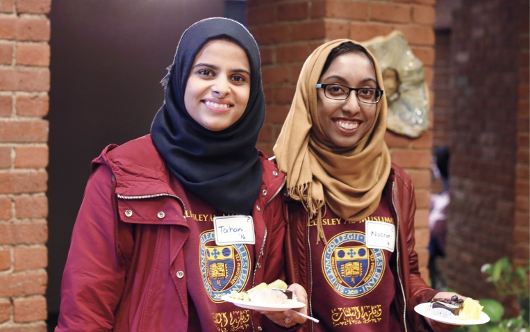 Two students wearing hijabs (head scarves) enjoy food at the Al-Muslimat 30th anniversary celebration.