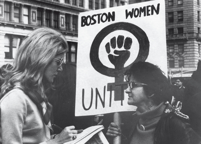 "Lynn Sherr interviewing a participant holding a sign reading ""UNITE"" with a female symbol and a fist during a women's rights march in 1970"