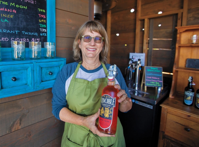 A photo shows Kelly Miller McCune holding a large bottle of her product at the Runcible Cidery in Oregon.