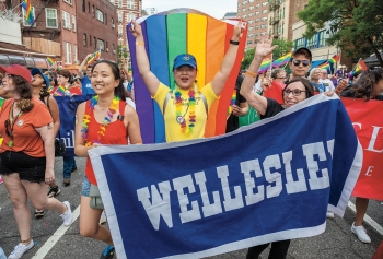 A photo shows Wellesley women marching with a rainbow flag and the Wellesley banner at the New York City Pride Parade in June.