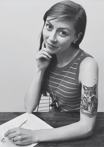 A black-and-white photo of author reveals her upper-arm tattoo of a fox holding a pen.