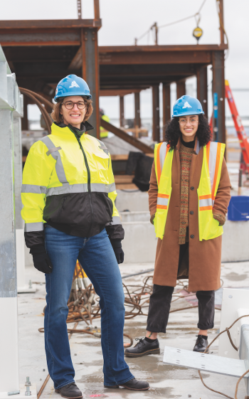 "Jahanara ""Jana"" Freedman '20 and  Samantha Hand Fratus '89 stand at a construction site for a 1,000-room hotel project in the Boston seaport district."